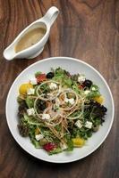 Salada grega com queijo feta e azeitonas com vinagrete cítrico na mesa de madeira foto