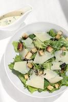 salada césar com queijo parmesão e croutons na mesa de madeira foto