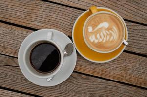 cappuccino com latte art e café puro em mesa de madeira foto