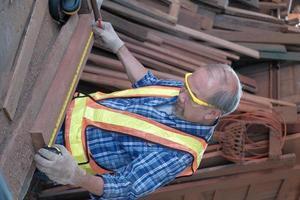 carpinteiro masculino asiático sênior, trabalhando em uma fábrica de madeira. foto