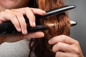 garota endireita o cabelo encaracolado com um ferro. foto