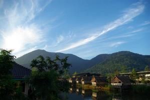 pela manhã, pequenas cabanas ao lado do lago e da vista da montanha foto