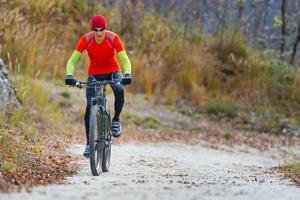 motociclista em estrada de terra na montanha foto