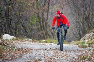 motociclista com mountain bike em estrada de terra foto