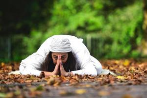 posição de ioga entre as folhas de outono no parque foto