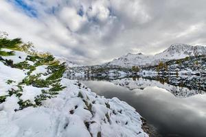 caminhando ao lado do lago alpino com neve foto