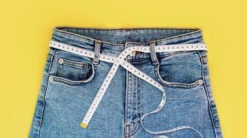 fita métrica e jeans em um fundo amarelo brilhante foto