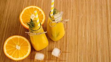 garrafas de suco de laranja e canudos de papel. bebida gelada em um dia ensolarado foto
