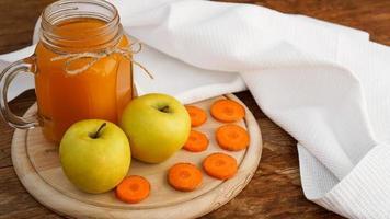suco de maçã e cenoura em vidro, vegetais frescos e frutas em madeira foto