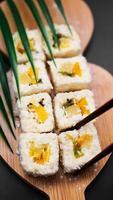 sobremesa sushi. rolinhos de sushi doce de kiwi, abacaxi e banana foto
