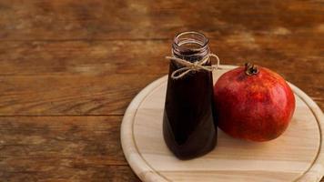 romãs maduras com suco em fundo de madeira. foto