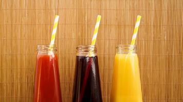 três bebidas multicoloridas nas garrafas em um fundo de madeira de bambu foto