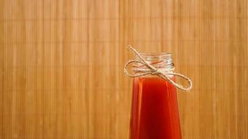 garrafa de suco de tomate em fundo de madeira foto