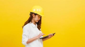 engenheira asiática usando tablet digital sobre fundo amarelo. foto