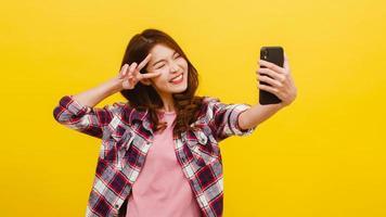 mulher asiática fazendo foto de selfie no telefone com expressão positiva.