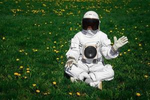 astronauta futurista com um capacete sentado em um gramado verde entre flores foto