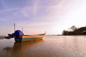 barco perto da praia quando o sol se põe foto