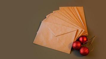 composição de natal. envelopes artesanais e bolas vermelhas foto