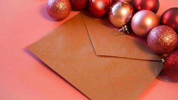 envelope de papel artesanal com bolas vermelhas e rosa de natal em rosa foto