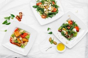 três pratos brancos com salada, rúcula e azeitonas no fundo branco foto