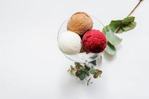 tigela de vidro com bolas coloridas de sorvete no fundo branco foto