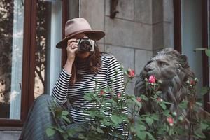 linda mulher com chapéu tira uma foto com câmera antiquada