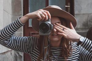 linda mulher com chapéu tirando foto com a câmera antiga