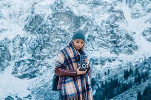 garota com uma câmera velha vintage em um fundo de montanhas de neve foto