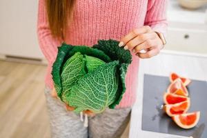 mulher segurando repolho verde na cozinha foto