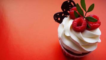 sobremesa doce, bolinho com creme de manteiga e framboesa no vermelho foto