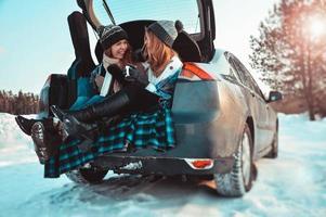 amigos felizes na floresta de inverno. duas meninas sentadas no porta-malas bebendo café foto
