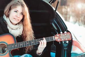 garota tocando violão sentada no porta-malas do carro foto