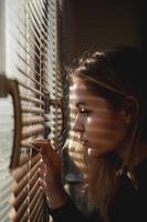bela jovem olha através das cortinas foto