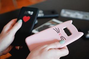 mãos segurando capas de smartphone coloridas. foto