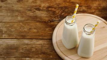duas garrafas de leite orgânico rústico na mesa de madeira foto