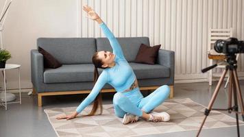 mulher blogueira em roupas esportivas grava vídeo para a câmera em casa foto