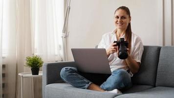jovem feliz com câmera fotográfica usando laptop em casa foto