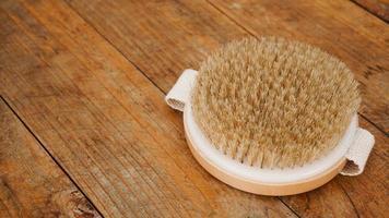 escova de massagem seca feita de materiais naturais em um fundo de madeira foto