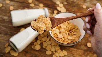 flocos de milho saudáveis e leite e uma colher de pau na mesa de madeira. foto