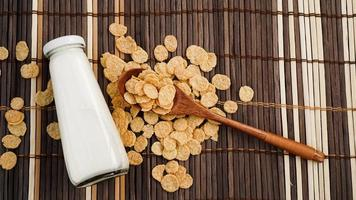 flocos de milho saudáveis e leite e uma colher de pau em um guardanapo de bambu. foto