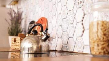 chaleira de metal no fogão. cozinha moderna e aconchegante foto