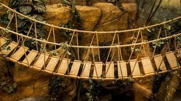 aventura ponte suspensa de corda de madeira na floresta tropical foto