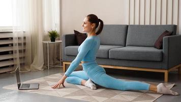 bela jovem fazendo exercícios de fitness em casa com seu laptop foto