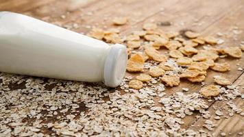 garrafa de leite fresco com fundo de madeira com aveia e cereais foto