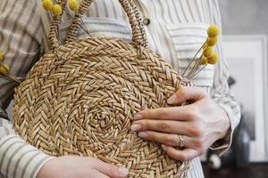 Mãos de mulher com bolsa de vime nude elegante e elegante e bolsa de palha foto