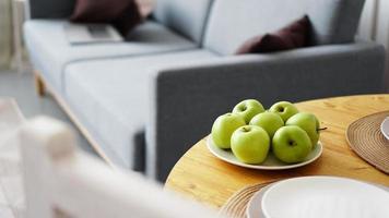 maçãs verdes em um prato branco sobre uma mesa de madeira foto