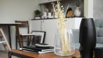 um vaso com flores secas sobre uma mesa. escandinavo foto