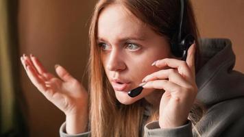 operador de garota confusa com fone de ouvido. trabalho remoto foto
