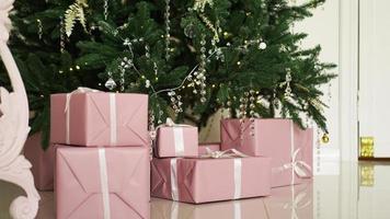 caixas de presentes rosa com fitas sob a árvore de natal foto