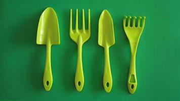 conjunto de ferramentas de jardim verdes sobre fundo verde foto